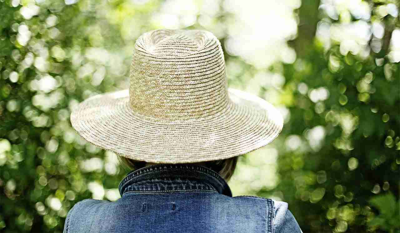 woman standing outside wearing a hat